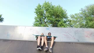 Man and woman sitting on ramp at skatepark, watching their friend skateboarding