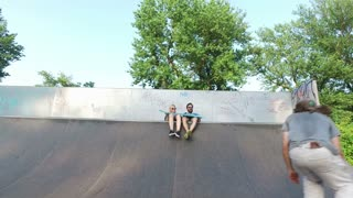 Man and woman watching their friend skateboarding on ramp at skatepark