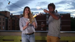 Man and woman waving with firework candles and toasting with champagne