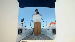 Man at wheel steering sailboat on Adriatic sea in Croatia