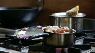 Man boiling meat in pot on a kitchen stove.