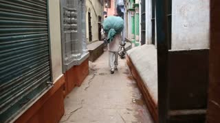 Man carrying a large sack on his back in narrow street in Varanasi, back view.