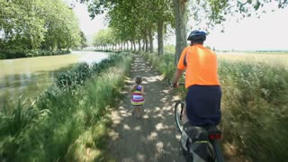 Man cycling along dirt track beside river under trees with grand daughter