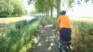 Man cycling along dirt track beside river under trees