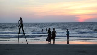 Man dancing on crutches on beach at sunset, with people watching.