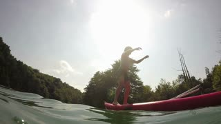Man doing backflip from canoe into water