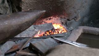 Man heating a blade in hot coal in workshop in Varanasi.