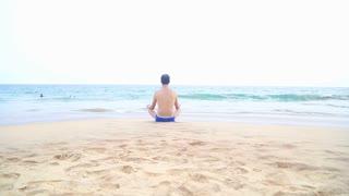 Man meditating on sandy beach in the tropics