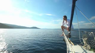 Man on the bow of sailing boat on Mediterranean sea.