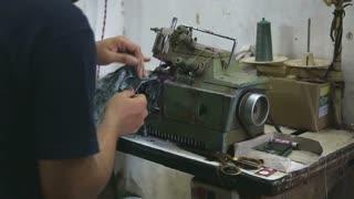 Man preparing to work on a sewing machine in workshop in Mumbai, closeup.