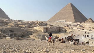 Man riding camel in desert landscape in front of the pyramids at Giza