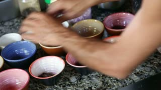 Man serving food in colorful pots.