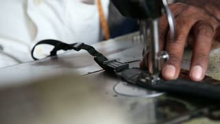Man sewing on a sewing machine, closeup.