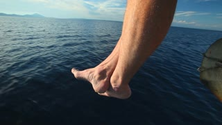 Man sitting at the bow of the boat with feet and legs overboard