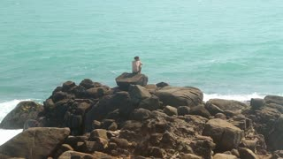 Man sitting on a huge boulder on a beach and looking at the sea