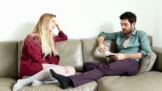 Man sitting on comfortable couch speaking to handsome woman