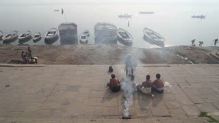 Man talking to boys by Ganges river, with boats and river in background.