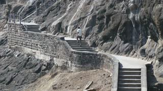 Man walking up the stairs outside of Aurangabad caves.