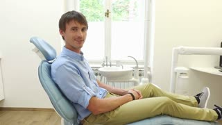 Man with beautiful white smile sitting in dental chair and looking at camera