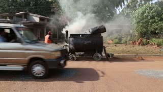 Man working on smoky machinery on street while vehicles pass by.
