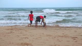 MATARA, SRI LANKA - MARCH 2014: The view of a three local kids playing on a beach in Matara. Matara is a major city in the southern coast in Sri Lanka.