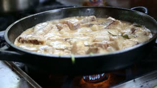 Meat and sauce boiling in pan on a kitchen stove.