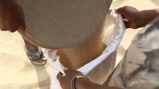 Men pouring collected sand to sack.