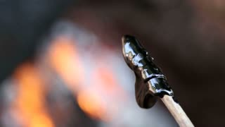 Metall mater melting by fire and shaping around a stick.