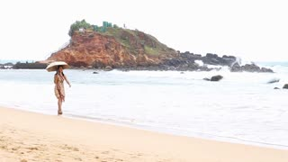 MIRISSA, SRI LANKA - MARCH 2014: Japanese tourist walking down beach with umbrella as sun protection. This small sandy tropical beach boasts some of Sri Lanka�۪s best and most stunning sunsets and sunrises.