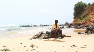 MIRISSA, SRI LANKA - MARCH 2014: Local man sitting on a rock on the beach. This small sandy tropical beach boasts some of Sri Lanka�۪s best and most stunning sunsets and sunrises.