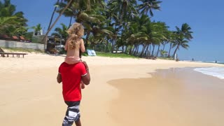 MIRISSA, SRI LANKA - MARCH 2014: Man carrying little girl on his shoulders on the beach. This small tropical beach boasts some of Sri Lanka�۪s best and most stunning sunsets and sunrises.