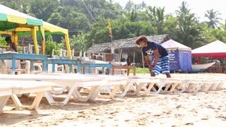 MIRISSA, SRI LANKA - MARCH 2014: Man preparing sun beds for tourists on beach in Mirissa. This beach village lives mostly from tourism.
