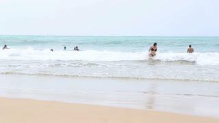 MIRISSA, SRI LANKA - MARCH 2014: People enjoying the ocean in Mirissa. This small sandy tropical beach boasts some of Sri Lanka�۪s best and most stunning sunsets and sunrises.