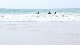 MIRISSA, SRI LANKA - MARCH 2014: The view of a five local boys enjoying in the ocean in Mirissa. This small sandy tropical beach boasts some of Sri Lanka�۪s best and most stunning sunsets and sunrises.