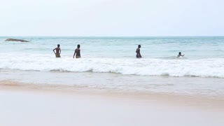 MIRISSA, SRI LANKA - MARCH 2014: The view of a three local boys jumping into the ocean in Mirissa. This small sandy tropical beach boasts some of Sri Lanka�۪s best and most stunning sunsets and sunrises.