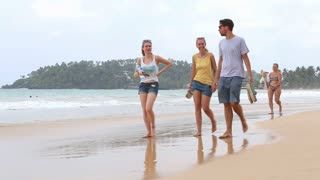 MIRISSA, SRI LANKA - MARCH 2014: Tourists walking by on sandy beach barefoot with shoes in their hands. This small sandy tropical beach boasts some of Sri Lanka�۪s best and most stunning sunsets and sunrises.