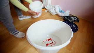 Mixing red paint in bucket of white paint