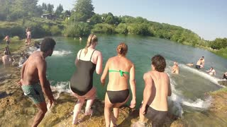 MREZNICA RIVER, CROATIA - 19 JULY 2015: Back view of young friends jumping into river on beautiful sunny day, graded, in slow motion. People cooling down in the river.