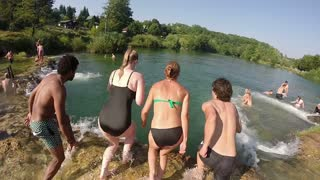 MREZNICA RIVER, CROATIA - 19 JULY 2015: Back view of young friends jumping into river on beautiful sunny day, in slow motion. People cooling down in the river.