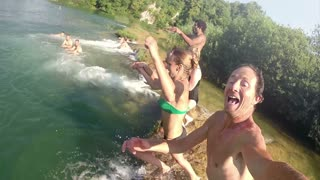 MREZNICA RIVER, CROATIA - 19 JULY 2015: Happy handsome man holding camera while jumping into river with friends, graded, in slow motion. People relaxing and cooling down in the river.