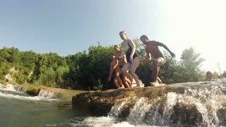 MREZNICA RIVER, CROATIA - 19 JULY 2015: Side view of happy young friends jumping into river on beautiful sunny day, graded, in slow motion. People relaxing and cooling down in the river.