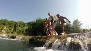 MREZNICA RIVER, CROATIA - 19 JULY 2015: Side view of happy young friends jumping into river on beautiful sunny day, in slow motion. People relaxing and cooling down in the river.