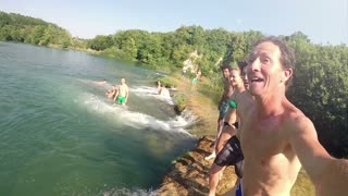MREZNICA RIVER, CROATIA - 19 JULY 2015: Young friends holding hands while jumping into river, graded, in slow motion. People relaxing and cooling down in the river.