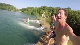 MREZNICA RIVER, CROATIA - 19 JULY 2015: Young friends holding hands while jumping into river, in slow motion. People relaxing and cooling down in the river.