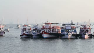 MUMBAI, INDIA - 10 JANUARY 2015: Boats in a bay at the seaside of Mumbai, with crowds standing on the dock.