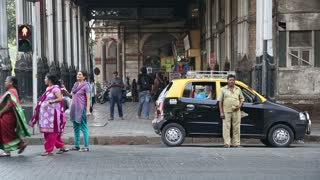 MUMBAI, INDIA - 10 JANUARY 2015: Driver standing in front of taxi on street in Mumbai while people pass by.