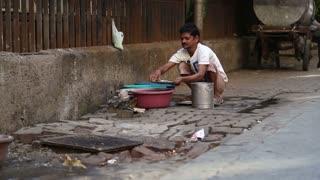 MUMBAI, INDIA - 10 JANUARY 2015: Indian man washing dishes by a street drain-away in Mumbai.