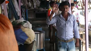 MUMBAI, INDIA - 10 JANUARY 2015: Indian man waving in a manufactory, while people work in the background.