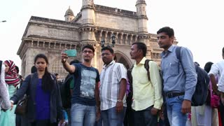 MUMBAI, INDIA - 10 JANUARY 2015: Indian men posing in front of Gateway to India, while people pass by.