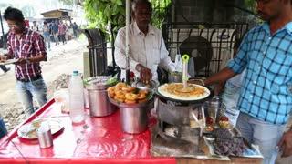 MUMBAI, INDIA - 10 JANUARY 2015: Indian men preparing and selling local food at the street stand in Mumbai.
